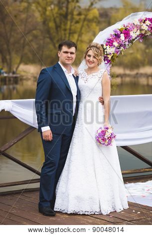 Just Married Couple Standing On Pier At Wedding Ceremony