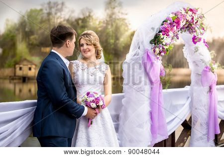 Beautiful Smiling Newlyweds Posing At Floral Arch At Sunset