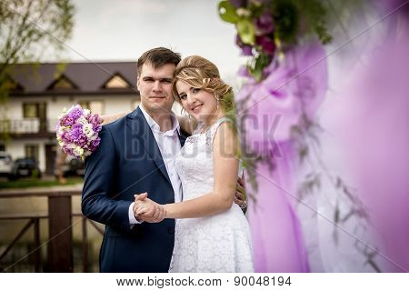 Bride And Groom Hugging Against Decorated Ceremony Place