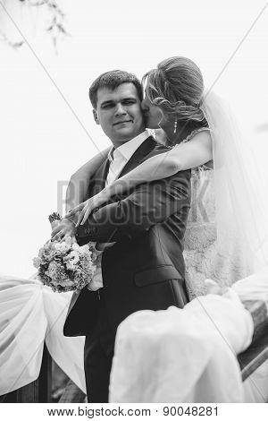 Black And White Portrait Of Bride Hugging Grooms Shoulder
