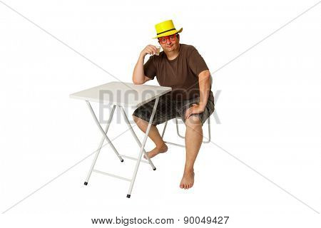 Brazilian man sat on a pub table drinking a lemon brandy isolated on white background.