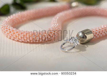 Pink Necklace From Beads On A Textile Background