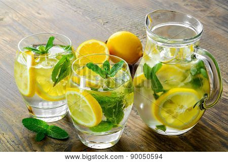 Lemonade in two glass and lemon with mint on the table