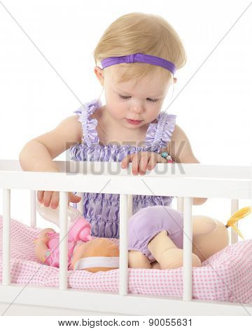 An adorable 2-year-old feeding her baby doll over the railing of her toy crib.  On a white background.