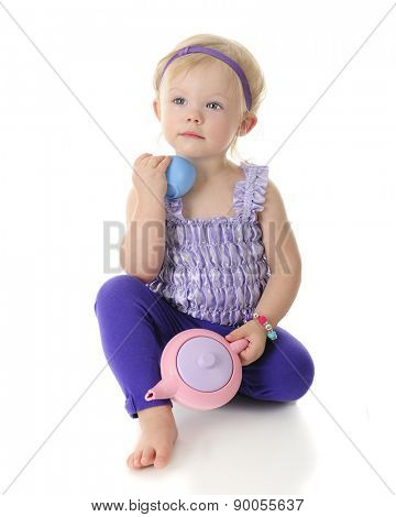 An adorable 2-year-old lovingly holding her tea pot and a cup from her toy tea set.  On a white background.