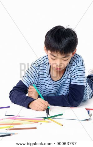 Portrait of a schoolboy lying down and writing in notebook.