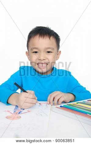 Portrait of a schoolboy sitting and writing in notebook.