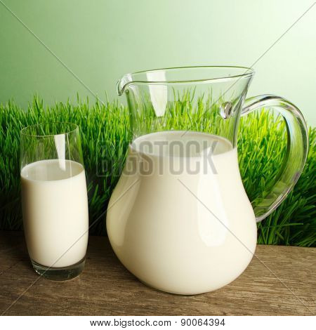 Glass of milk and jar on fresh grass meadow background