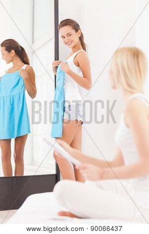 Young woman standing near the mirror with blue dress