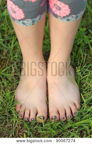 Close-up View Of Little Shoeless Girl Toes On Feet At Green Grass