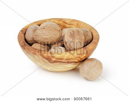 whole dried nutmegs in bowl, isolated