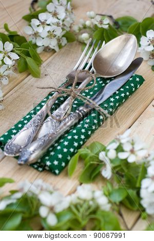 Fork, Spoon And Knife Lying On A Wooden Background Among The Branches Of A Flowering Tree