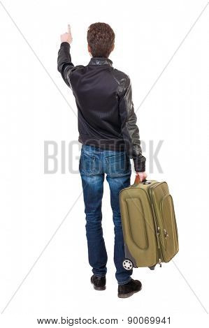 back view of  pointing man  with suitcase. brunette guy in a leather jacket pointing .  backside view of person.   guy with a travel bag on wheels looking at something at the top