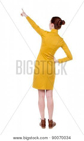 back view of woman. Young woman in vest presses down on something. Isolated over white background. Rear view people collection. backside view of person.  Beautiful slim girl in a strict dress.
