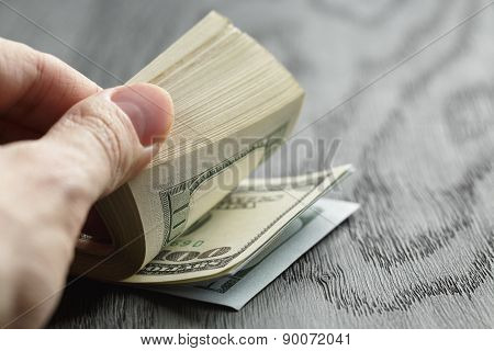man hands counting dollar notes on wood table