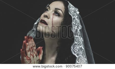 Praying, concept virgin, religion, woman with white headdress and gold crown