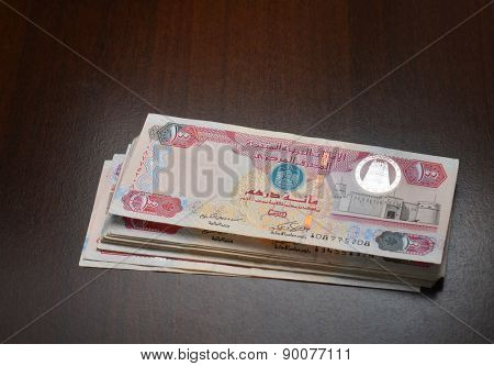 Bundle of Hundred dirhams currency notes on dark background.