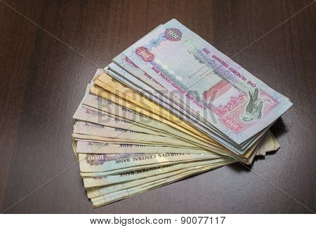 Spread of assorted currency notes of United Arab Emirates on dark background.