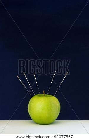 Acupuncture Needles Stuck Into A Green Apple As A Symbol