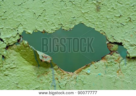 Hole In Old Green Metal Wall.