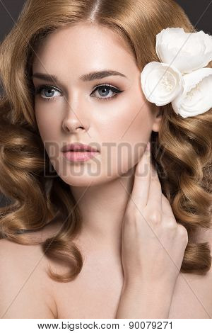 Portrait of a beautiful woman in the image of the bride with flowers in her hair.