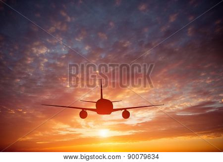 Airplane in the sky at a  beautiful sunset clouds