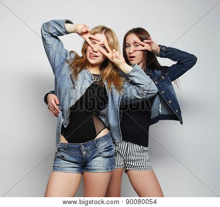 Two young girl hipster friends standing together, having fun.Over grey background.