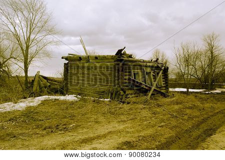Retro collapsed wooden house without a roof in the countryside