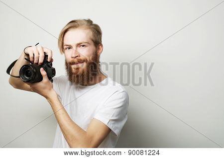 life style, tehnology and travel concept: bearded man wearing white t-shirt with a digital camera isolated on a white background