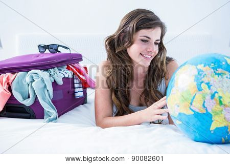 Woman with a suitcase and globe while lying on her bed at home in the bedroom