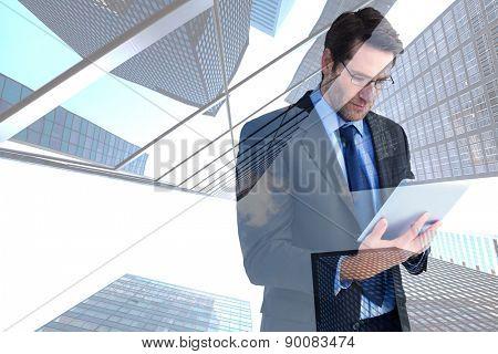 Businessman using a tablet computer against skyscraper