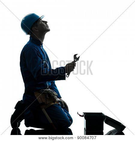 one  repairman worker despair praying silhouette in studio on white background