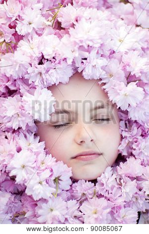 Face Of Small Girl Among Flowers