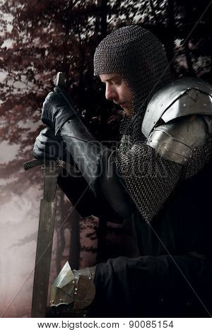 Ancient knight in metal armor with sword standing on one knee