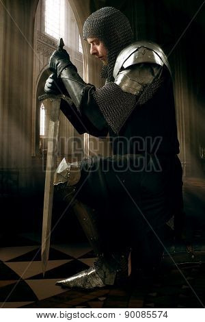 Ancient knight in metal armor with sword standing on one knee in a palace