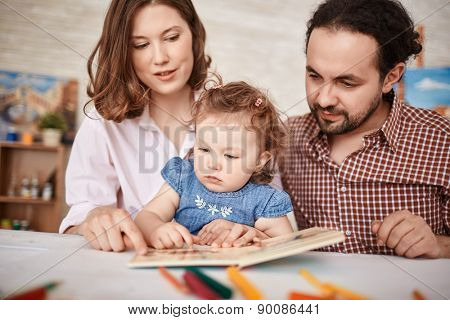 Young parents and their small daughter reading together