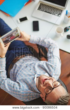 Ecstatic businessman with touchpad sitting by his workplace