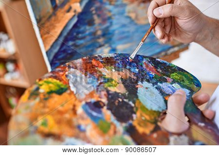 Hand of artist with paintbrush mixing oilpaints