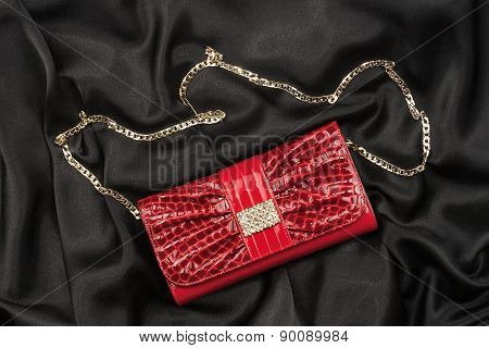 Red Lacquer Bag Lying On A Black Silk