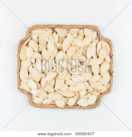 Frame Made Of Rope With  Pumpkin  Seeds  Lying On A White Background