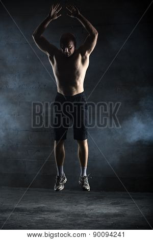 Bald athlete topless jumping up