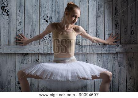 Ballerina standing near a wooden wall