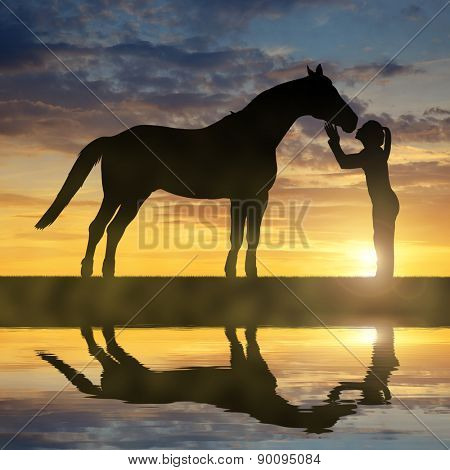 Silhouette of a girl giving a kiss horse in sunset
