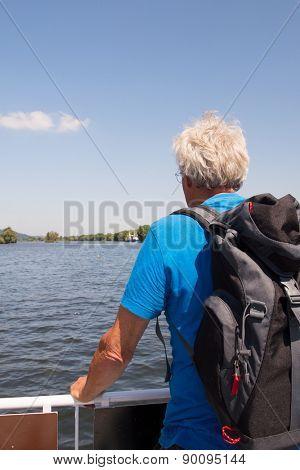 Senior man with backpack in nature landscape