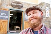 stock photo of barber  - Portrait Of Hipster Barber Standing Outside Shop - JPG