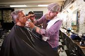 foto of facial piercings  - Male Barber Giving Client Shave In Shop - JPG