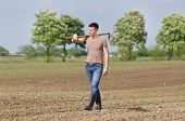 stock photo of hoe  - Attractive young farmer with hoe walking in corn field in spring - JPG