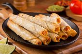 picture of cheese platter  - A platter of delicious chicken taquitos with salsa guacamole and lime - JPG