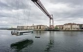 stock photo of suspension  - Closeup Wide view of the Bizkaia suspension bridge against cloudy sky and boat in Portugal  - JPG