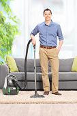 image of couch  - Full length portrait of a young man posing with a vacuum cleaner in front of a gray couch at home - JPG